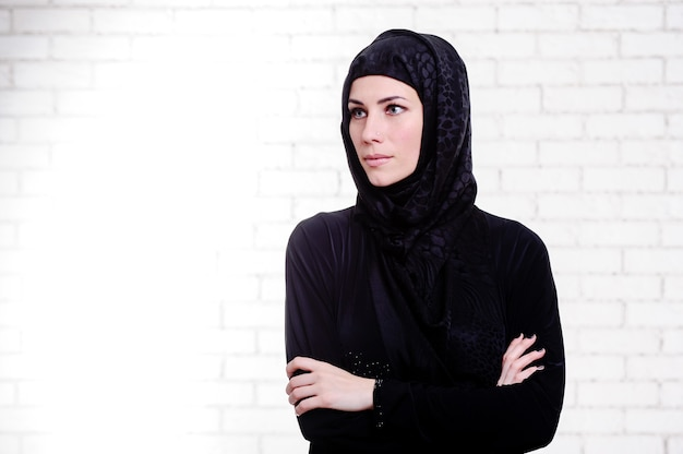 Young arabic woman dressed traditional arabic dress poses indoor.