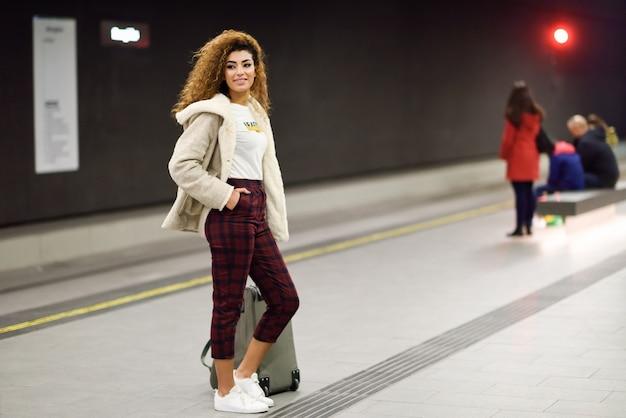 地下鉄の駅で彼女の電車を待っている若いアラビア人女性。