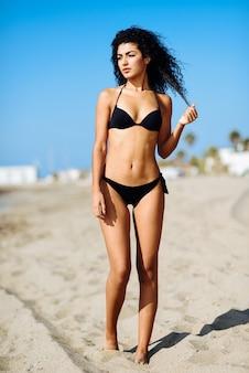 Молодая арабская женщина с красивым телом в купальники на тропическом пляже.
