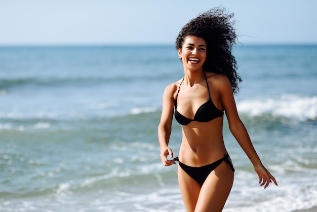Young arabic woman with beautiful body in swimwear smiling in a tropical beach.