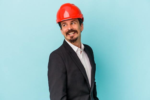 Young architect caucasian man isolated on blue background looks aside smiling, cheerful and pleasant.