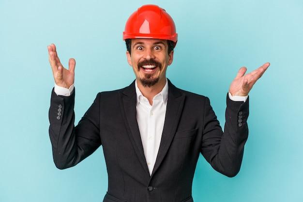 青い背景に孤立した若い建築家白人男性は、嬉しい驚きを受け取り、興奮し、手を上げます。