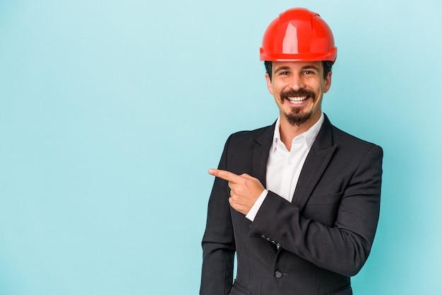 青の背景に孤立した若い建築家白人男性は、笑顔で脇を指して、空白のスペースで何かを示しています。