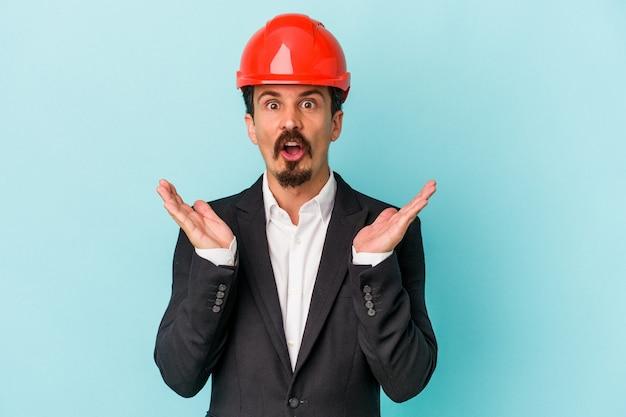 파란색 배경에 격리된 젊은 건축가 백인 남자가 놀라고 충격을 받았습니다.