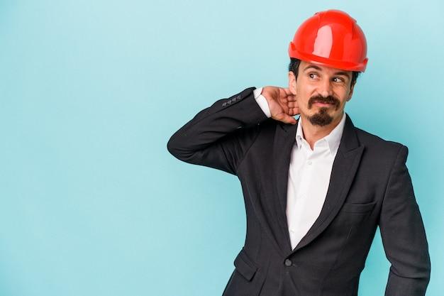 頭の後ろに触れて、考えて、選択をする青い背景に孤立した若い建築家白人男性。