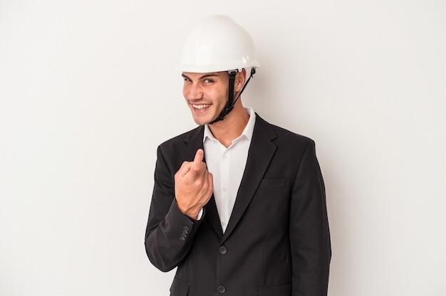 誘うようにあなたに指で指している白い背景に孤立した若い建築家白人男性が近づいています。