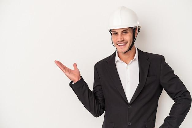 手のひらにコピースペースを示し、腰に別の手を保持している白い背景で隔離の若い建築家白人男性。