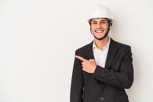 笑顔と脇を指して、空白のスペースで何かを示して、白い背景で隔離の若い建築家白人男性。
