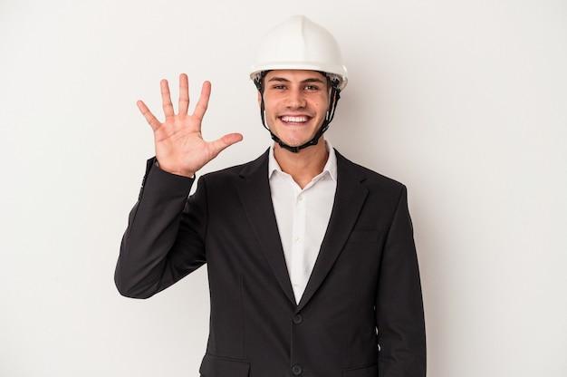 指で5番を示す陽気な笑顔の白い背景で隔離の若い建築家白人男性。