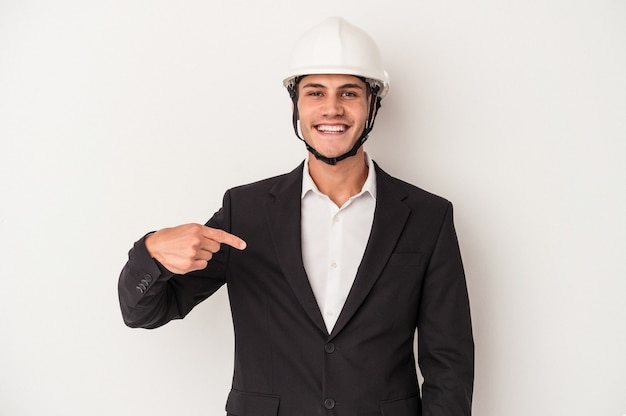 Young architect caucasian man isolated on white background person pointing by hand to a shirt copy space, proud and confident
