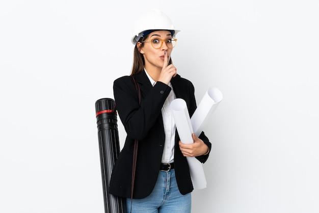 헬멧을 가진 젊은 건축가 백인 여자와 침묵 제스처를하는 동안 청사진을 들고
