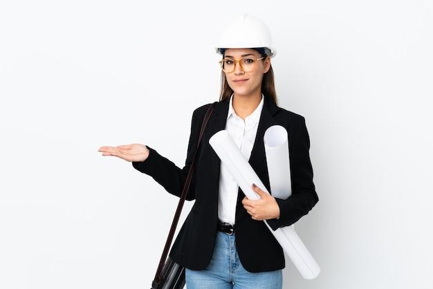 헬멧을 가진 젊은 건축가 백인 여자와 와서 초대하기 위해 손을 옆으로 뻗어 청사진을 들고