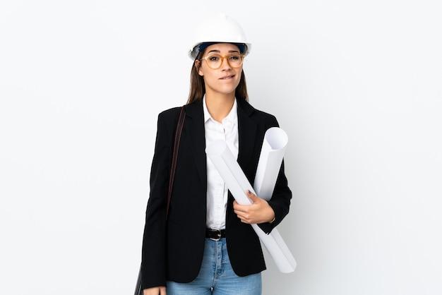 젊은 건축가 백인 여자 헬멧과 청사진을 들고 의심을 가지고 혼란스러운 얼굴 표정으로