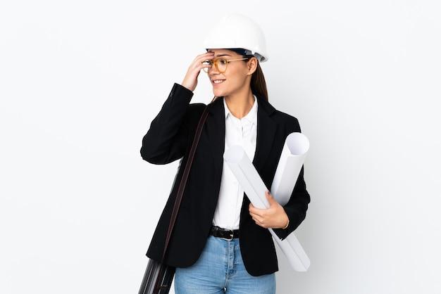 헬멧과 웃음을 통해 청사진을 들고 젊은 건축가 백인 여자