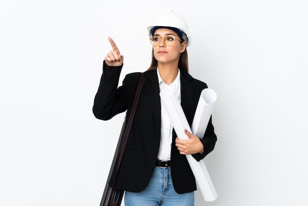 헬멧을 가진 젊은 건축가 백인 여자와 투명 화면에 감동을 통해 청사진을 들고
