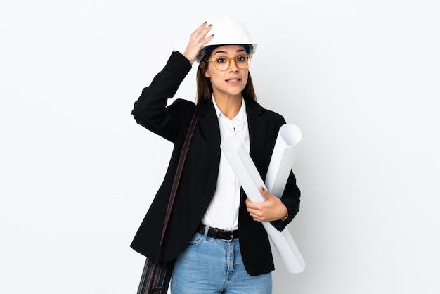 젊은 건축가 백인 여자 헬멧과 깜짝 표정으로 청사진을 들고