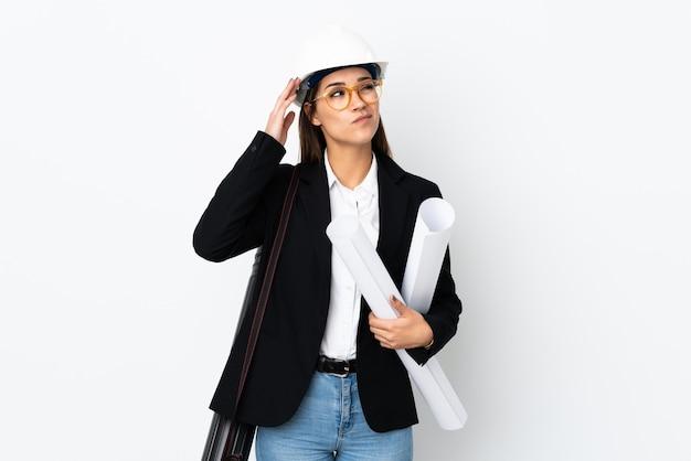 Кавказская женщина молодой архитектор в шлеме и держит чертежи