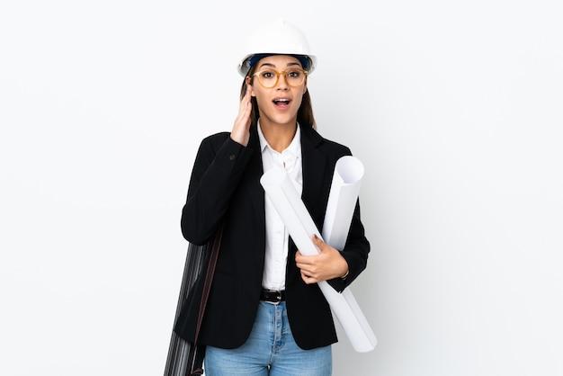 ヘルメットと青写真を保持している若い建築家白人女性