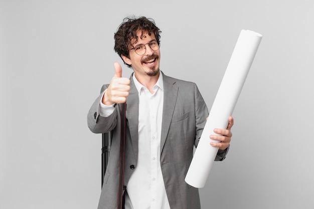 若い建築家は誇りを感じ、親指を立てて前向きに笑っています