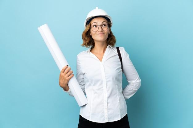 헬멧을 가진 젊은 건축가 그루지야 여자와 격리 된 배경 위에 청사진을 들고 찾고
