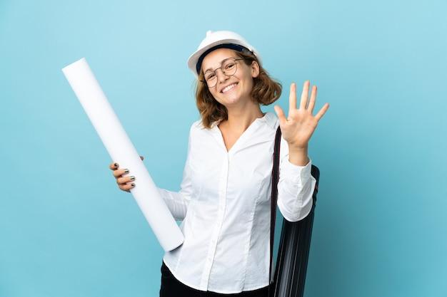 Молодой архитектор грузинская женщина в шлеме и держит чертежи на изолированном фоне, считая пять пальцами