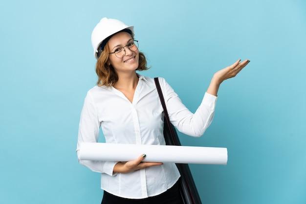 헬멧을 가진 젊은 건축가 그루지야 여자와 고립 된 배경 위에 청사진을 들고 와서 초대하기 위해 손을 옆으로 확장
