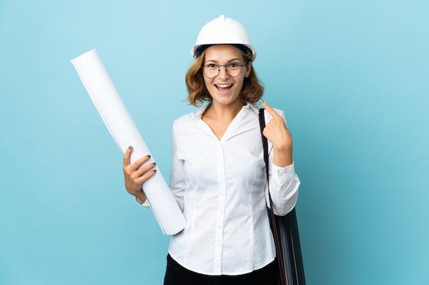 헬멧을 가진 젊은 건축가 그루지야 여자와 제스처를 엄지 손가락을주는 격리 된 배경 위에 청사진을 들고