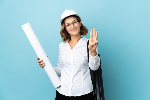 젊은 건축가 그루지야 여자 헬멧과 격리 된 배경 위에 청사진을 들고 행복 하 고 손가락으로 세 세