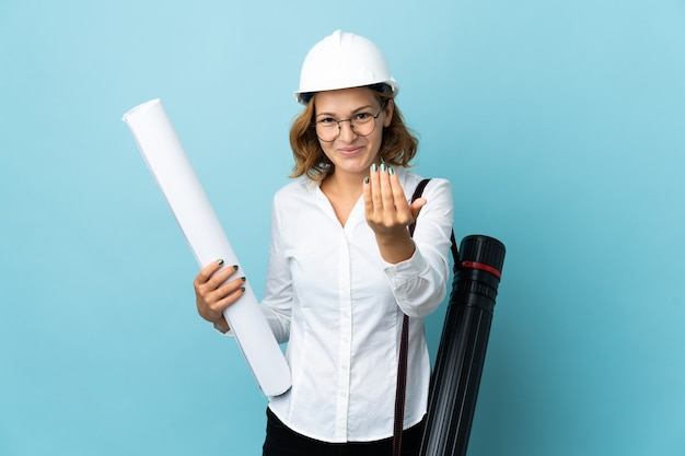 젊은 건축가 그루지야 여자 헬멧과 손으로와 서 초대 격리 된 배경 위에 청사진을 들고. 와줘서 행복해 프리미엄 사진