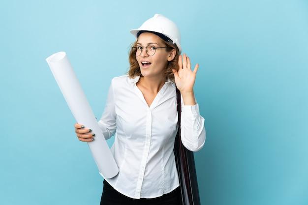 젊은 건축가 그루지야 여자 헬멧과 격리 된 배경 위에 청사진을 들고 귀에 손을 넣어 뭔가를 듣고