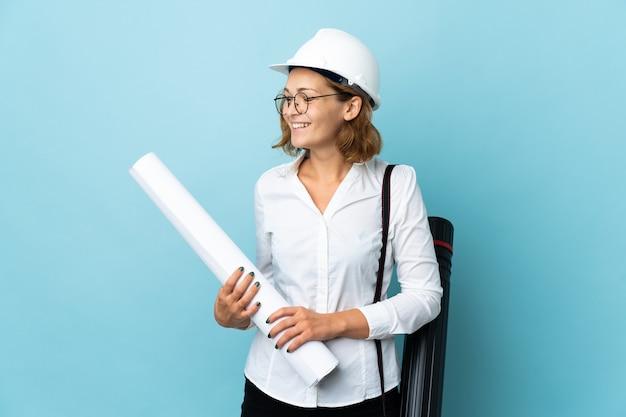 헬멧과 측면을 찾고 격리 된 배경 위에 청사진을 들고 젊은 건축가 그루지야 여자