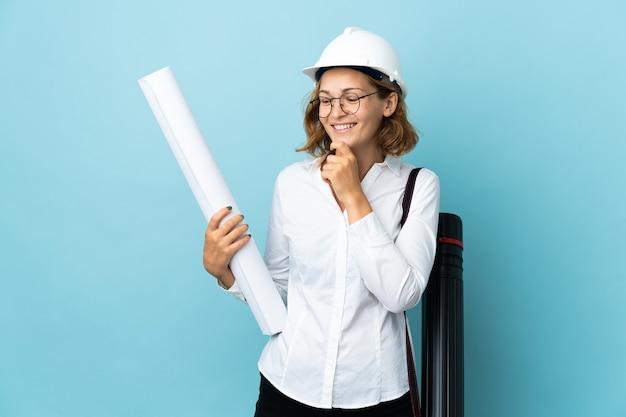헬멧을 가진 젊은 건축가 그루지야 여자와 측면을보고 웃고 격리 된 배경 위에 청사진을 들고