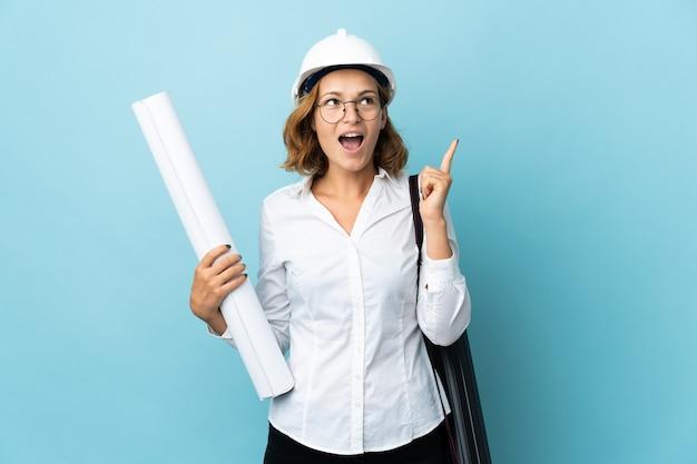 Молодой архитектор грузинская женщина в шлеме и держит чертежи на изолированном фоне, думая об идее, указывая пальцем вверх