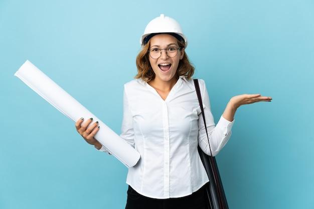 Молодой архитектор грузинская женщина в шлеме и держит чертежи на изолированном фоне с шокированным выражением лица
