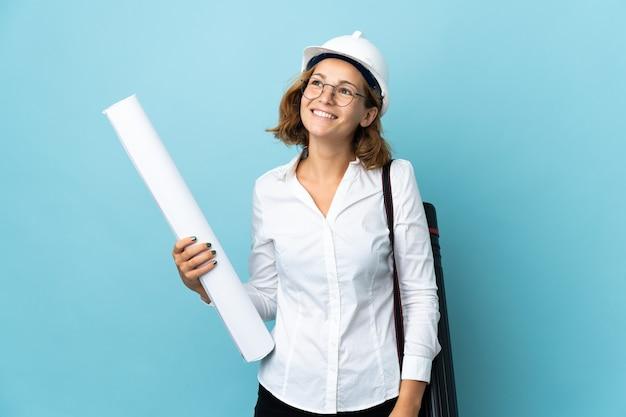 Молодой архитектор грузинская женщина в шлеме и держит чертежи над изолированным, думая об идее, глядя вверх