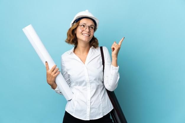 헬멧과 좋은 아이디어를 가리키는 격리 된 벽 위에 청사진을 들고 젊은 건축가 그루지야 여자