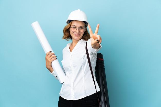 헬멧과 격리 된 벽에 청사진을 들고 웃 고 승리 기호를 보여주는 젊은 건축가 그루지야 여자