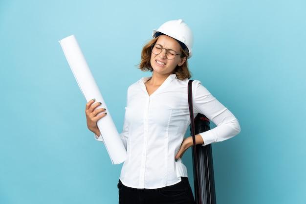 Молодой архитектор грузинская женщина в шлеме и держит чертежи над изолированной стеной, страдающей от боли в спине из-за того, что приложила усилие