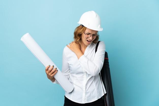 Молодой архитектор грузинская женщина в шлеме и держит чертежи над изолированной стеной, страдающей от боли в плече за то, что приложила усилие