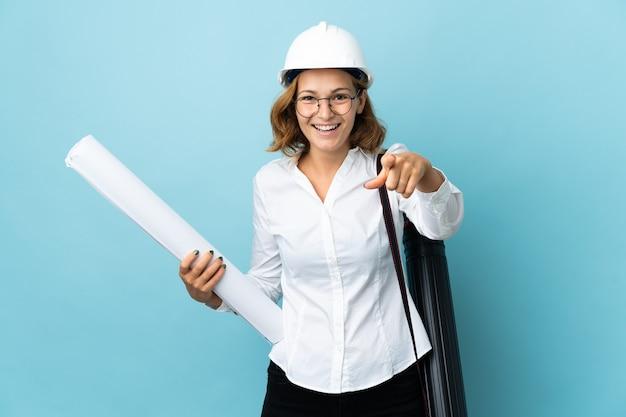 젊은 건축가 헬멧과 격리 된 벽에 청사진을 들고 그루지야 여자 놀라게하고 앞을 가리키는