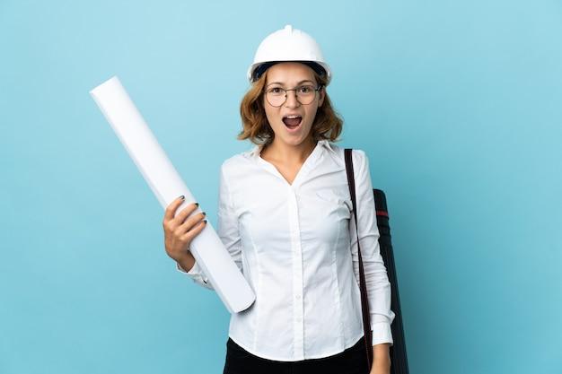 헬멧을 가진 젊은 건축가 그루지야 여자와 놀라운 표정으로 고립 된 벽 위에 청사진을 들고
