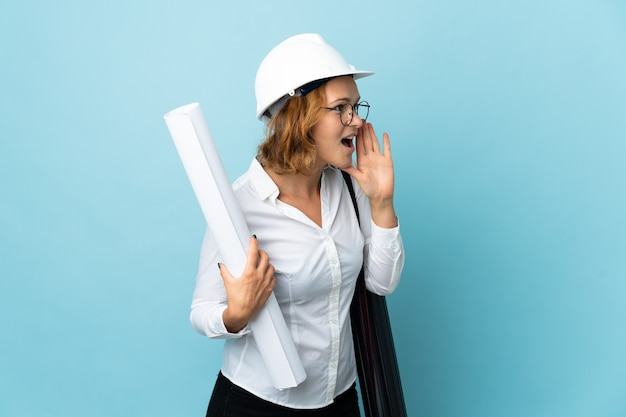 Young architect georgian woman with helmet and holding blueprints over isolated background shouting with mouth wide open to the side