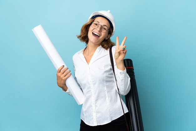 Young architect georgian woman with helmet and holding blueprints over isolated background smiling and showing victory sign