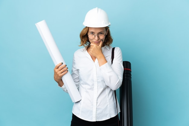 Young architect georgian woman with helmet and holding blueprints over isolated background thinking