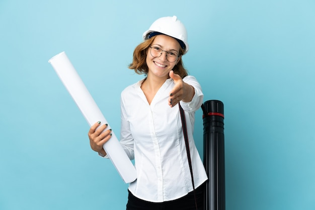 Young architect georgian woman with helmet and holding blueprints over isolated shaking hands for closing a good deal