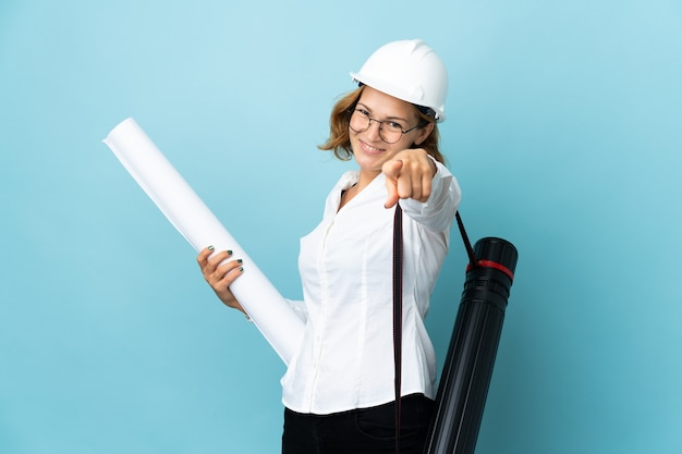 Young architect georgian woman with helmet and holding blueprints