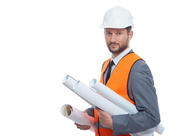 Молодой архитектор, держащий много чертежей планов зданий