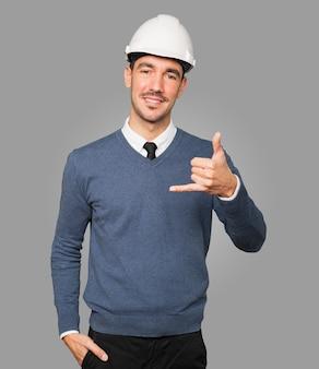 그의 손으로 전화 제스처를 만드는 젊은 건축가