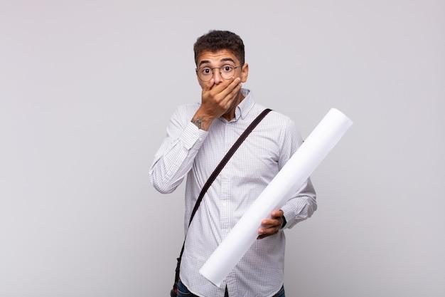 Молодой архитектор закрывает рот руками с шокированным, удивленным выражением лица, хранит секрет или говорит: ой