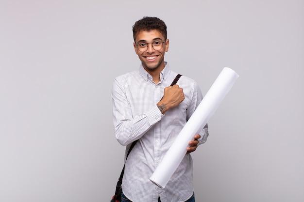 挑戦に直面したり、良い結果を祝ったりするときに、幸せで、前向きで、成功し、やる気を感じている若い建築家の男